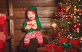 Happy baby elf helper of Santa with gift at christmas tree Royalty Free Stock Photo