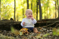 Happy Baby Girl in Autumn Woods under Yellow Maple Trees Royalty Free Stock Photo