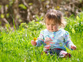 Happy baby girl a cute looking sits in long grass Royalty Free Stock Images