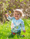 Happy baby girl a cute looking sits in long grass Royalty Free Stock Photos
