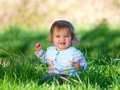 Happy baby girl a cute looking sits in long grass Stock Photos