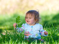 Happy baby girl a cute looking sits in long grass Royalty Free Stock Photo