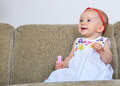 Happy baby girl with hairbrush little smiles while she lies on the couch a in hands Stock Photos