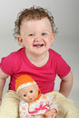 Happy baby girl with her doll on grey background Stock Image