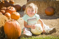 Happy baby girl holding a pumpkin at the pumpkin patch adorable in rustic ranch setting Royalty Free Stock Photo