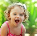 Happy baby girl joy with opened mouth outdoor summer background closeup Stock Image
