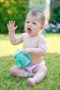 A happy baby girl in pants holding a bottle and put a hand up screaming Royalty Free Stock Photography