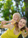 Happy baby girl piggybacking mother Royalty Free Stock Images