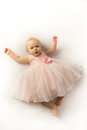 Happy baby girl in pink frilly party dress a serene little dressed a lays on a white background Stock Images
