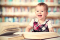 Happy baby girl reading a book in a library cute Royalty Free Stock Photo
