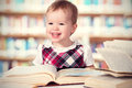 Happy baby girl reading a book in a library cute Royalty Free Stock Image