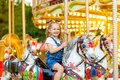 Happy baby girl rides a carousel on a horse in an amusement Park in summer Royalty Free Stock Photo