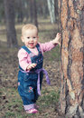 Happy baby girl stands on legs near a tree in the park outdoors jeans jumpsuit Stock Photo