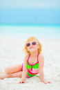 Happy baby girl in sunglasses sitting on beach Royalty Free Stock Photo