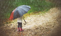 Happy baby girl with umbrella in the rain runs through an puddles Royalty Free Stock Photo