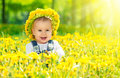 Happy baby girl in a wreath on meadow with yellow flowers on t beautiful little dandelions the nature the park Royalty Free Stock Photography