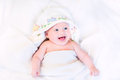 Happy baby in hand made cross stitch hooded towel laughing a after bath Stock Photography
