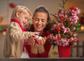 Happy baby helping mother decorate christmas tree in kitchen Royalty Free Stock Images