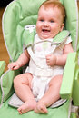 Happy baby in high chair Royalty Free Stock Photo