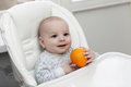 Happy baby holding orange Royalty Free Stock Photos