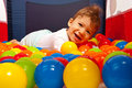 Happy baby laying on balls boy lying colorful in playpen Royalty Free Stock Images