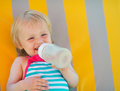 Happy baby laying on sunbed and drinking water Stock Photo