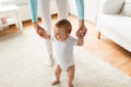 Happy baby learning to walk with mother help Royalty Free Stock Photo