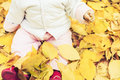 Happy baby outdoor at autumn park sitting on yellow leaves