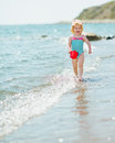 Happy baby with pail running along seashore Stock Images