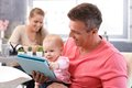 Happy baby reading e book sitting on father s lap mother sitting at background Royalty Free Stock Photos