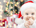 Happy baby in santa hat over christmas lights Royalty Free Stock Photo