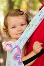 Happy baby sitting in a carrying sling. Stock Images