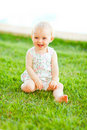 Happy baby sitting on grass Royalty Free Stock Images