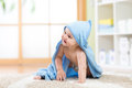 Happy baby in towel crawling on floor at home Royalty Free Stock Photo