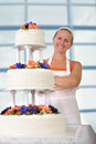 Happy baker lady smiling infront of her ruffled wedding cake happily large with apron and white bandanna has fondant ruffles on Royalty Free Stock Photography