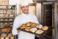 Happy baker showing tray of fresh bread Royalty Free Stock Photo