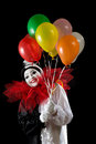 Happy with balloons female pierrot clown holding colorful Stock Images