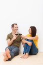 Happy barefoot young couple celebrating sitting on the wooden floor in their living room smiling and toasting each other with a Royalty Free Stock Photography