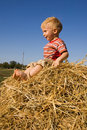 Happy barefooted baby boy sit on a hayrick Royalty Free Stock Photo