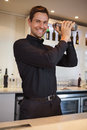 Happy bartender shaking cocktail at the bar Stock Photo