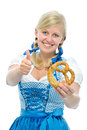 Happy bavarian girl in oktoberfest dirndl with pretzel shows thumb up Stock Photos