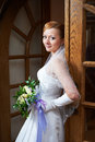 Happy beautiful bride with bouquet near doors in wedding dress Royalty Free Stock Photos
