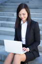 Happy beautiful business woman sitting on stairs and using lapto young laptop Royalty Free Stock Images