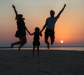 Happy beautiful family jumping on the beach at the sunset time Stock Photography