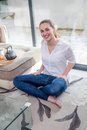 Happy beautiful girl with bare feet enjoying sitting on floor Royalty Free Stock Photo