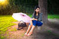 Happy beautiful girl having rest in the park a is outdoor at with her umbrella and bag Royalty Free Stock Image