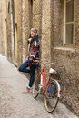 Happy beautiful girl is standing next to a bicycle in small stre street alley Stock Photos
