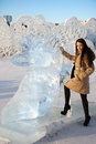 Happy beautiful girl stands near big ice shoe at sunny winter day Stock Image