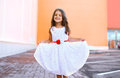 Happy beautiful little girl shows white dress and having fun