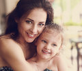 Happy beautiful mother cuddling her daughter with smile in cafe. Royalty Free Stock Photo
